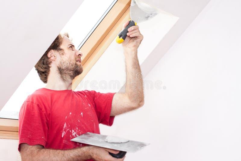 Lavoratore manuale con la parete che intonaca gli strumenti dentro una casa immagine stock