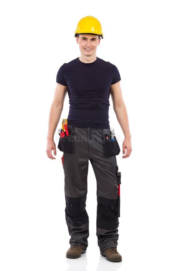 Lavoratore manuale nella posa gialla dell'elmetto protettivo fotografia stock libera da diritti