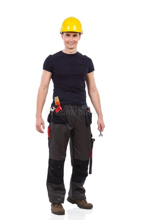 Lavoratore manuale nella posa gialla dell'elmetto protettivo fotografia stock