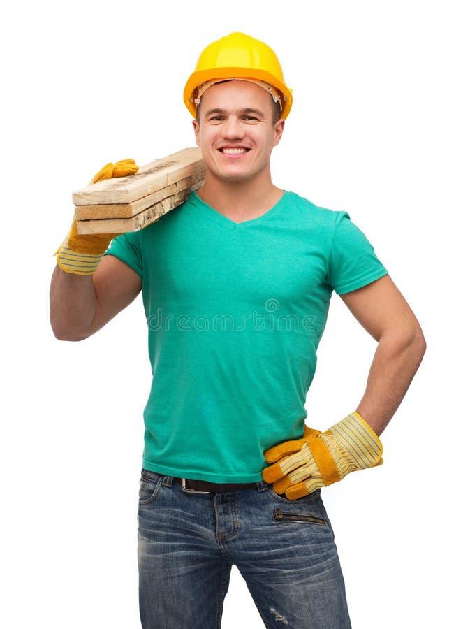 Lavoratore manuale sorridente in casco con i bordi di legno fotografie stock