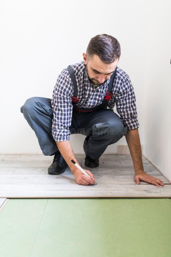 Lavoratore maschio che installa pavimentazione laminata, uomo che installa nuova pavimentazione laminata di legno Uomo che pone p fotografia stock libera da diritti