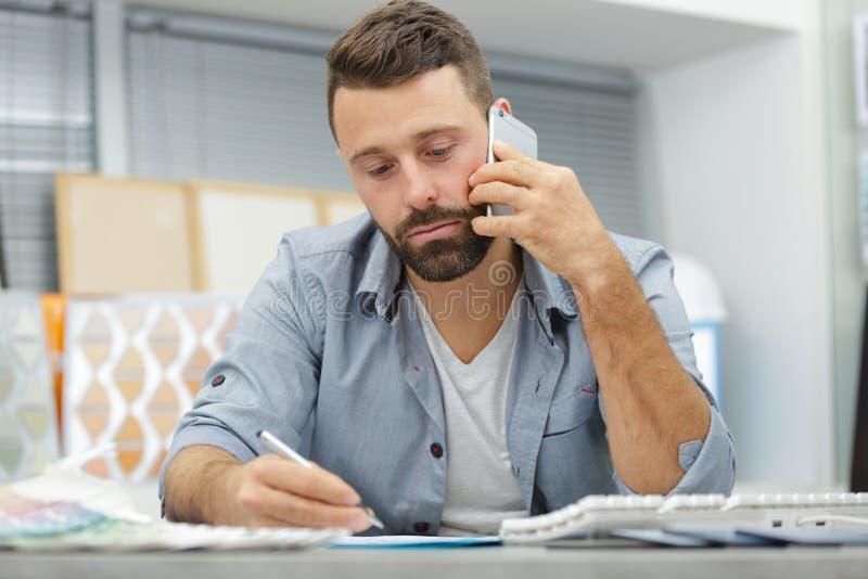 Lavoratore maschio che parla con cliente sullo smartphone fotografie stock libere da diritti