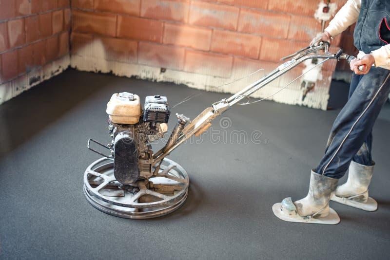 Lavoratore maschio con lo strumento della cazzuola di potere che finisce pavimento di calcestruzzo, superficie di calcestruzzo re fotografie stock