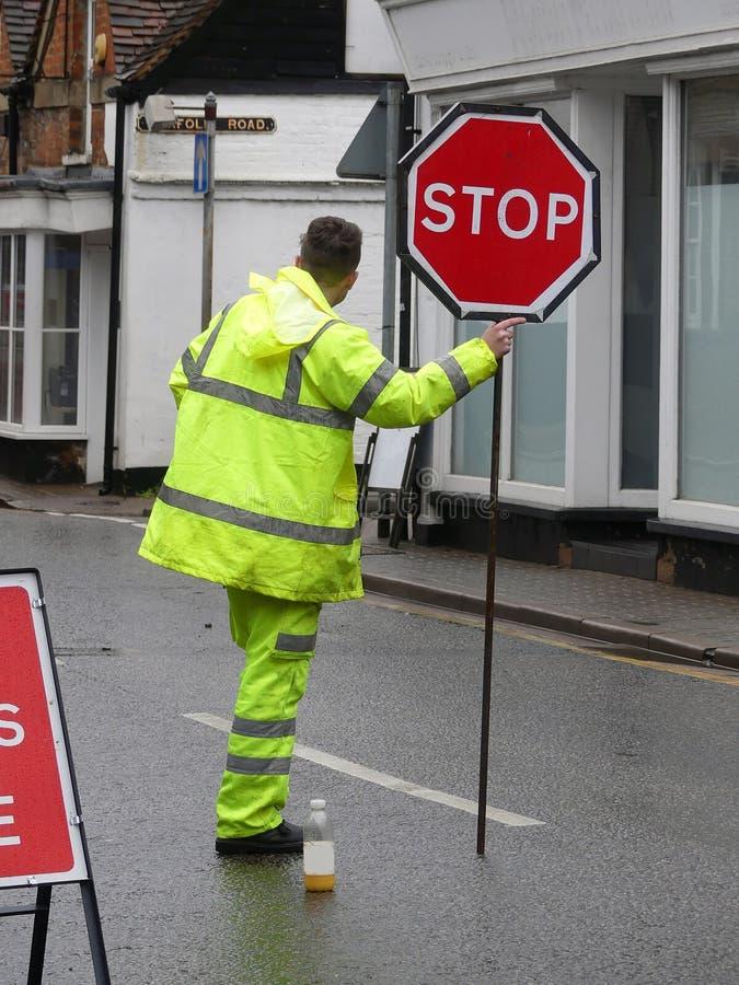 Lavoratore maschio della strada con il rivestimento giallo ed i pantaloni fluorescenti che tengono il segno rosso di arresto immagini stock libere da diritti