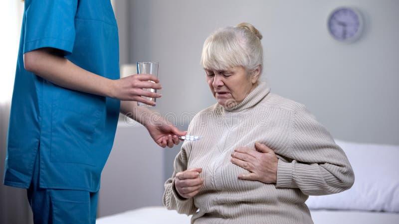Lavoratore medico che d? a pillole signora anziana che soffre dal dolore del cuore, trattamento fotografie stock