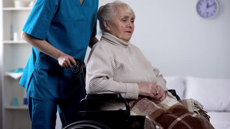 Lavoratore medico che prende cura circa signora senior turbata in sedia a rotelle, riabilitazione fotografia stock