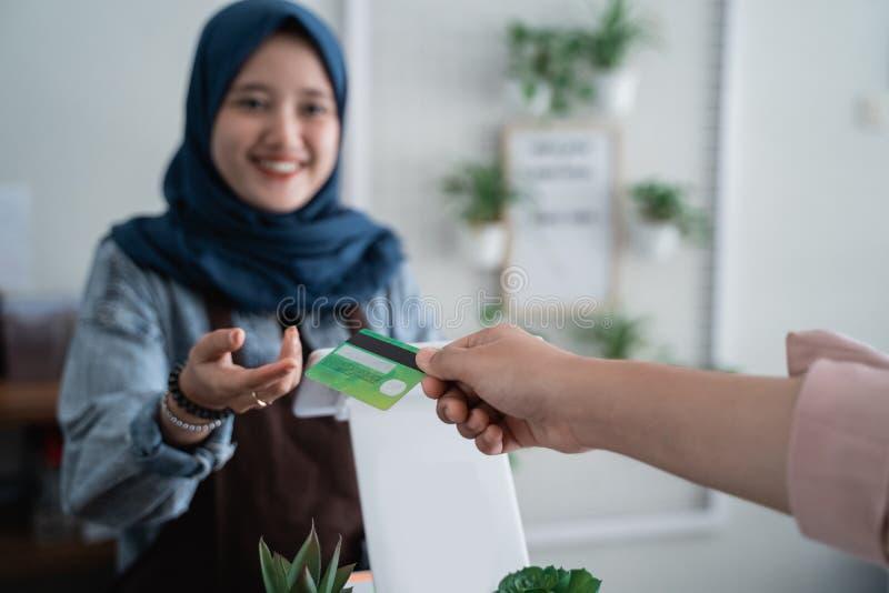 Lavoratore nel contatore del caffè che riceve pagamento fotografie stock libere da diritti