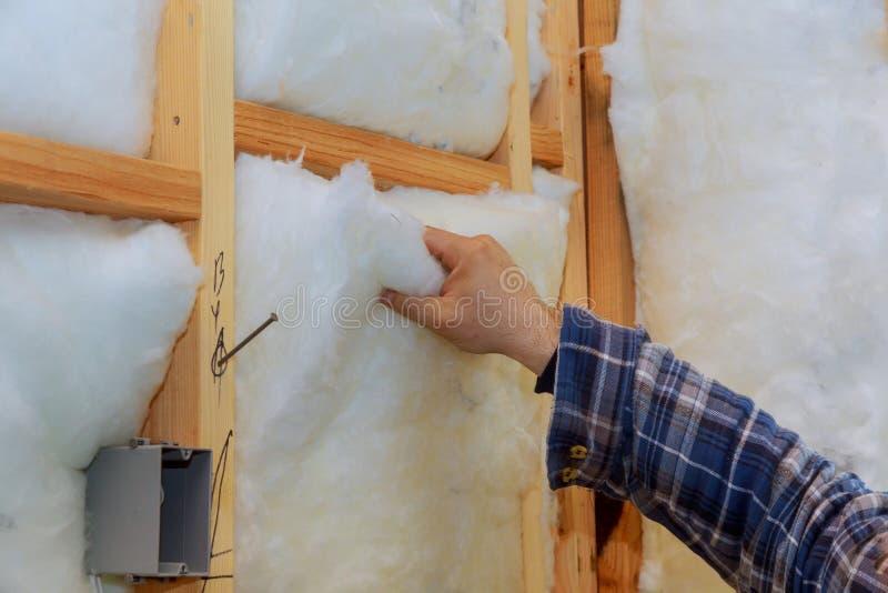 Lavoratore nell'isolamento d'isolamento della lana di roccia nel telaio di legno per le pareti future della casa per la casa cald immagini stock