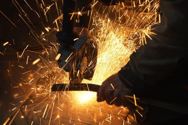 Lavoratore nella pianta Scintille durante il funzionamento di attrezzatura immagini stock libere da diritti