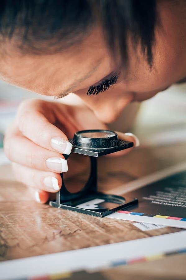 Lavoratore nella stampa e negli usi centar della stampa una lente d'ingrandimento fotografie stock