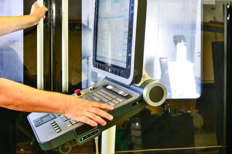 Lavoratore, operatore del pannello di controllo del programma dell'operazione di un centro di lavorazione di alta precisione di C immagine stock libera da diritti