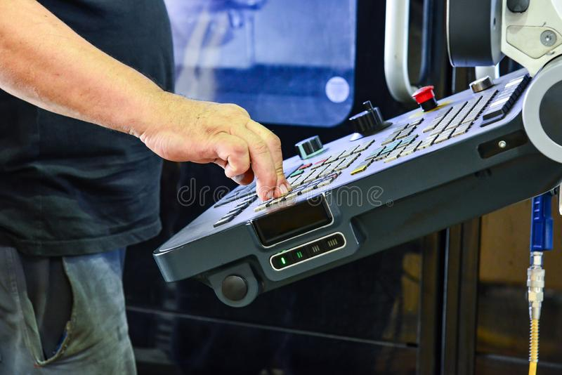 Lavoratore, operatore del pannello di controllo del programma dell'operazione di un centro di lavorazione di alta precisione di C fotografia stock