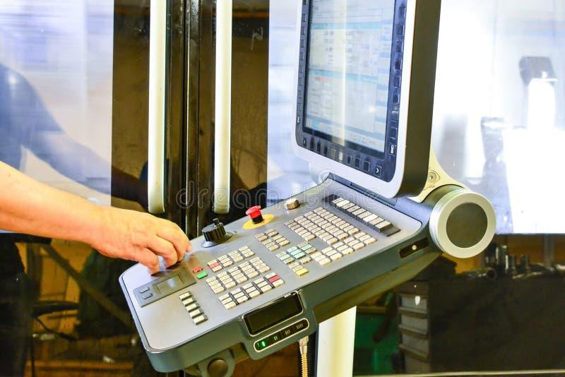 Lavoratore, operatore del pannello di controllo del programma dell'operazione di un centro di lavorazione di alta precisione di C immagine stock