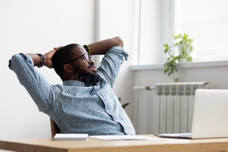 Lavoratore rilassato nero che si siede sulla sedia che esamina finestra fotografie stock