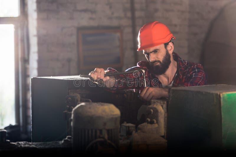 lavoratore serio in casco protettivo che ripara la macchina utensile fotografia stock libera da diritti
