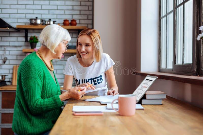 Lavoratore sociale di dipartimento che aiuta Dame grigio-dai capelli con le carte in ritardo di prestito immagine stock libera da diritti