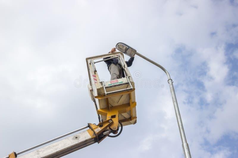 Lavoratore sopra un palo che ripara il fornitura 3 fotografia stock