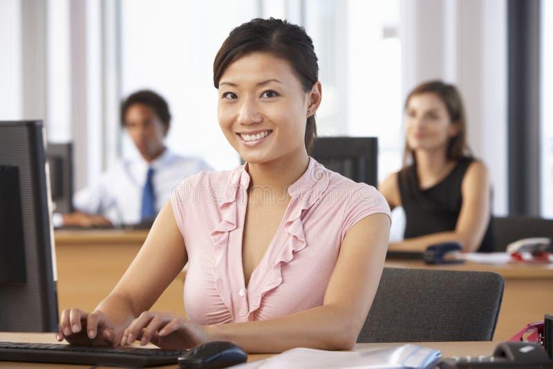 Lavoratore sorridente in ufficio occupato immagini stock