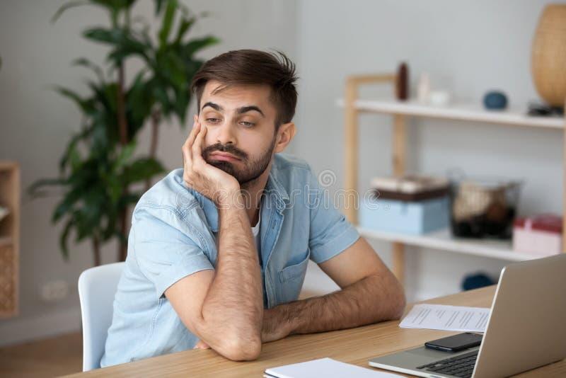 Lavoratore stanco che spreca tempo nel luogo di lavoro distratto dal lavoro d'alesaggio fotografie stock