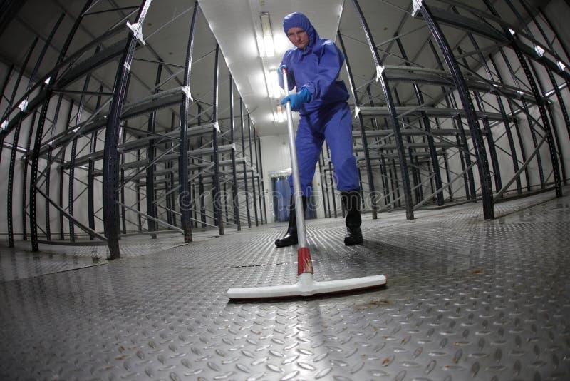 Lavoratore in tute blu e protettive che puliscono pavimento in deposito vuoto fotografia stock