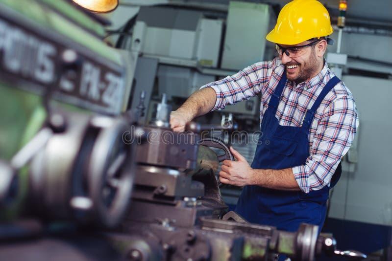 Lavoratore in uniforme che funziona in tornio manuale nella fabbrica dell'industria metalmeccanica immagini stock