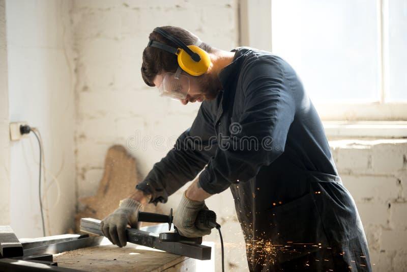 Lavoratore in vestiti protettivi che funzionano nell'officina fotografia stock