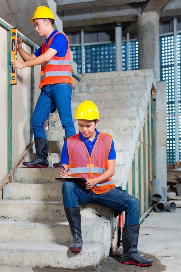 Lavoratori asiatici su costruzione o sul muro del cantiere immagini stock libere da diritti