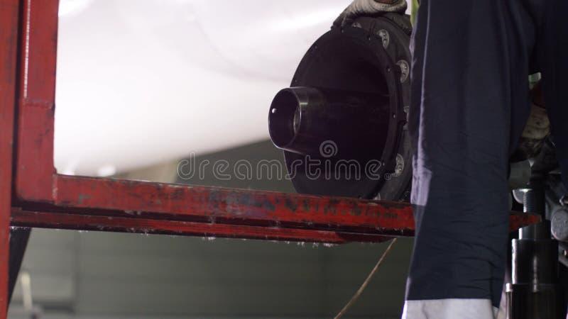 Lavoratori calmi che controllano la macchina ed i telai degli aerei Il meccanico di manutenzione di aerei ispeziona il telaio pia fotografia stock libera da diritti