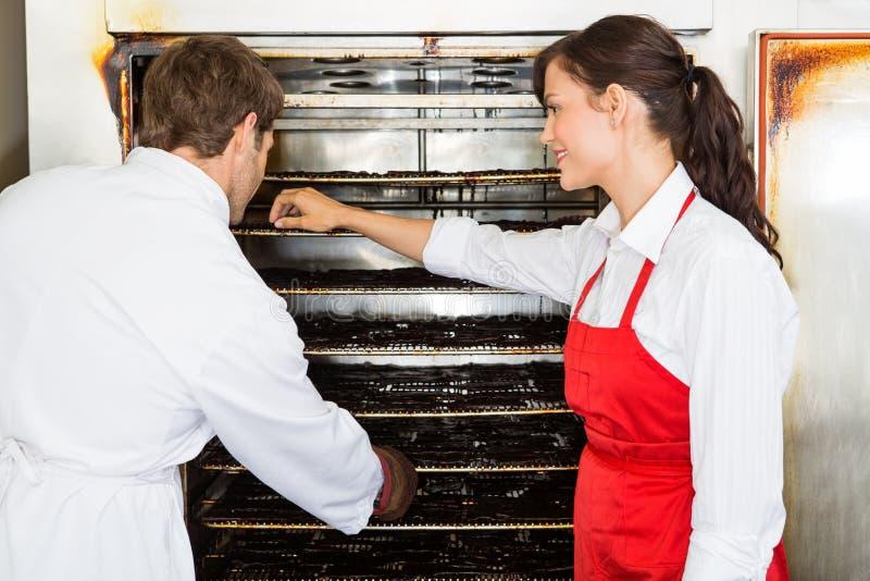 Lavoratori che asciugano carne nel negozio di Oven At Butcher immagine stock libera da diritti