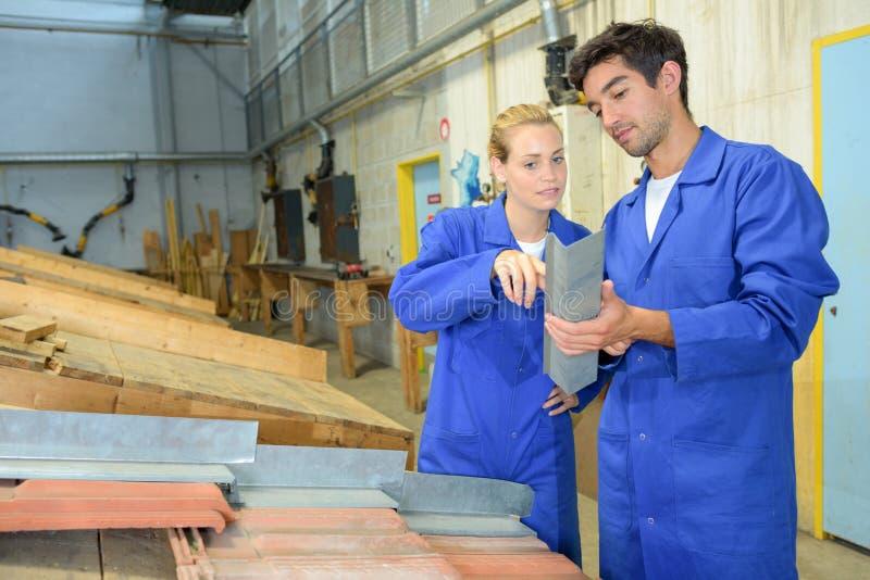 Lavoratori che esaminano il metallo ad angolo di destra immagine stock libera da diritti