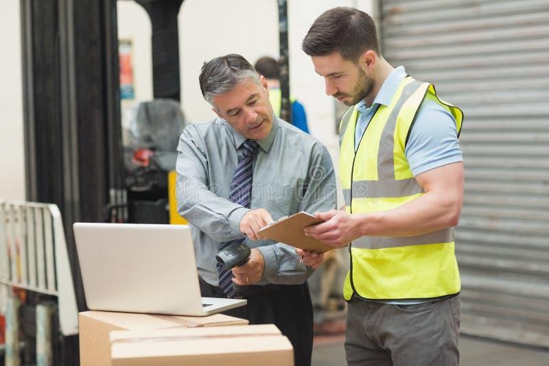 Lavoratori che esplorano pacchetto in magazzino immagini stock