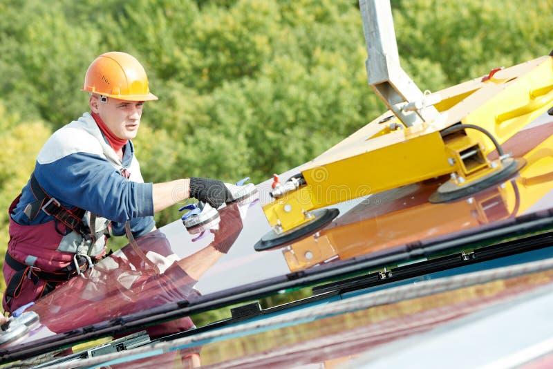 Lavoratori che installano finestra di vetro sulla costruzione immagine stock libera da diritti