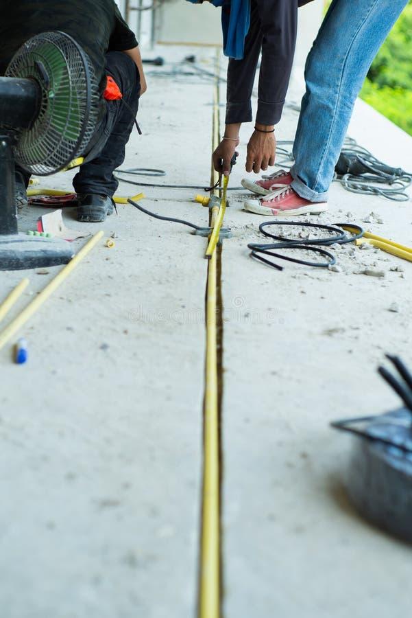 Lavoratori che installano il cavo elettrico ed il tubo nel und della casa fotografia stock libera da diritti