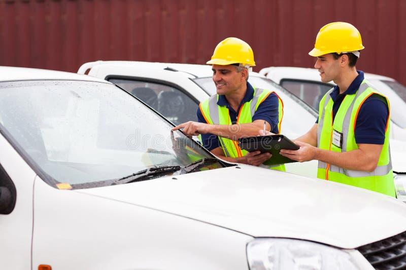 Lavoratori che ispezionano le automobili immagini stock