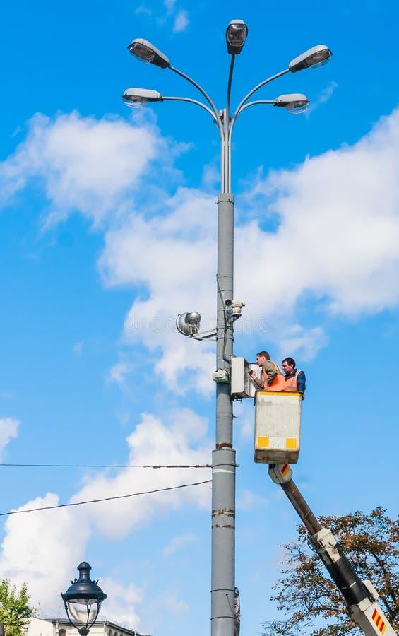 Lavoratori che rinnovano illuminazione urbana mosca immagine stock