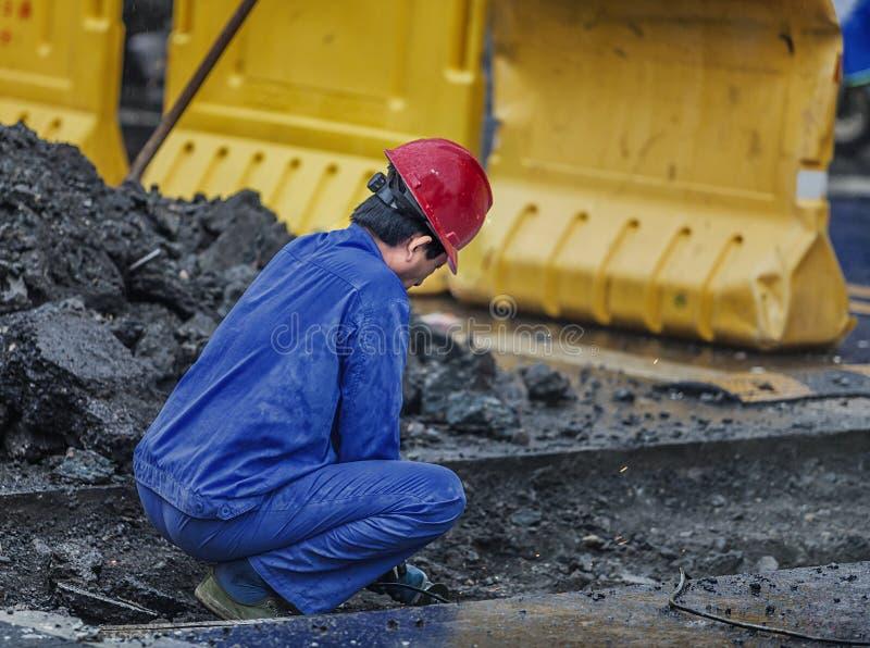Lavoratori che riparano i tubi sotterranei nella pioggia immagine stock libera da diritti