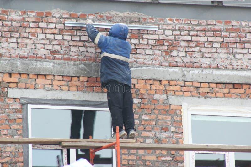 Lavoratori che stanno su una scala di legno nel legno, riparante la parete della costruzione immagine stock
