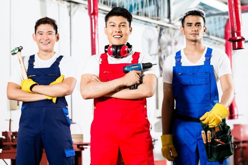 Lavoratori con gli strumenti in fabbrica industriale asiatica fotografia stock libera da diritti