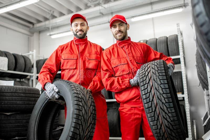 Lavoratori con le gomme di automobile al magazzino fotografie stock libere da diritti