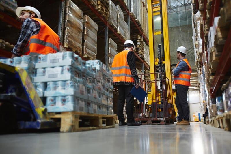 Lavoratori del magazzino che caricano le merci sul camion di forcella di portata fotografie stock libere da diritti