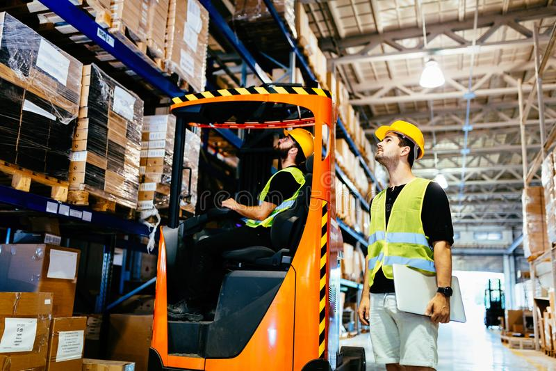 Lavoratori del magazzino che collaborano con il caricatore del carrello elevatore fotografie stock libere da diritti