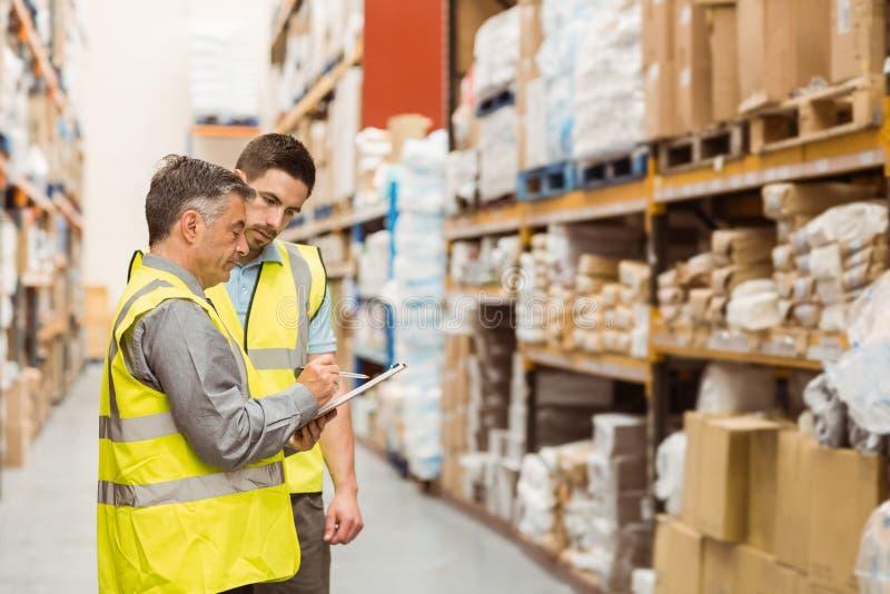 Lavoratori del magazzino che parlano insieme sul lavoro fotografia stock libera da diritti