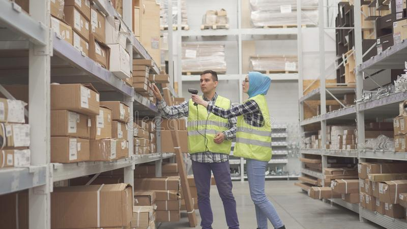Lavoratori del magazzino comunicare ed effettuare il codice a barre di stima dell'analizzatore immagine stock libera da diritti