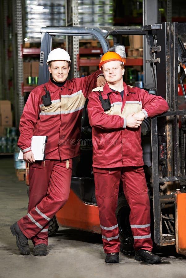 Lavoratori del magazzino davanti al carrello elevatore immagini stock