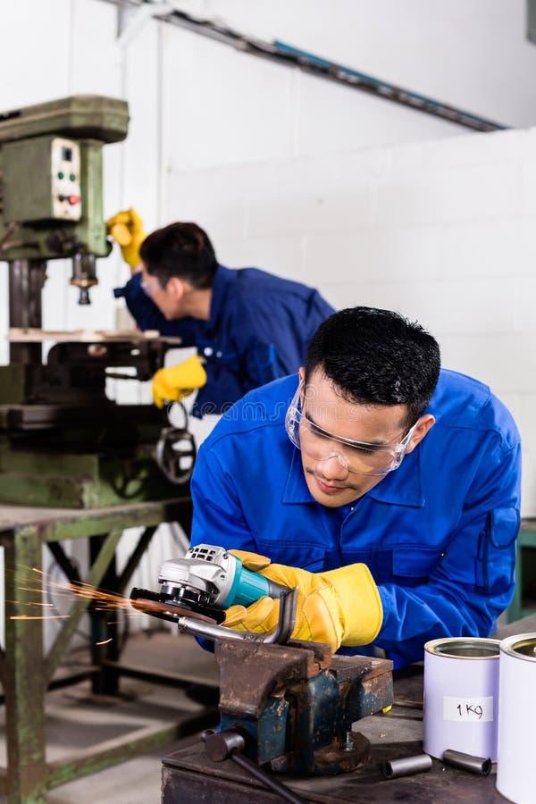 Lavoratori del metallo nella macinazione industriale dell'officina immagini stock