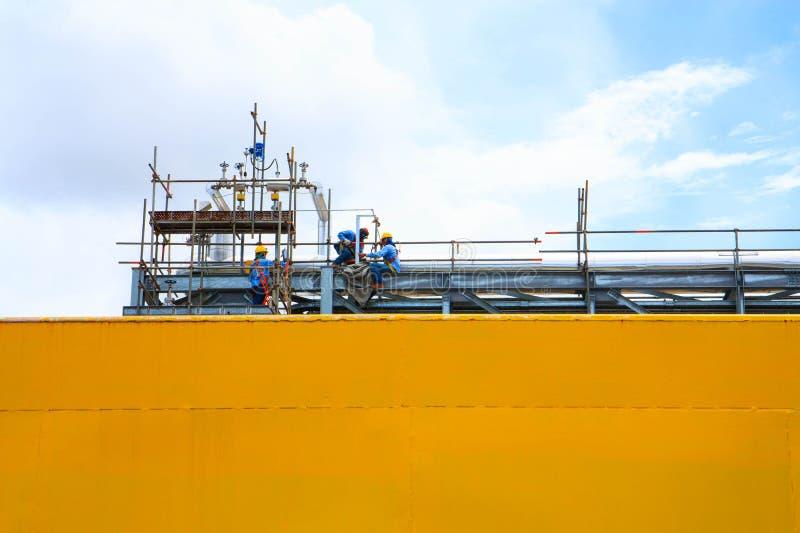 Lavoratori del petrolio che mantengono la linea del tubo della raffineria immagine stock