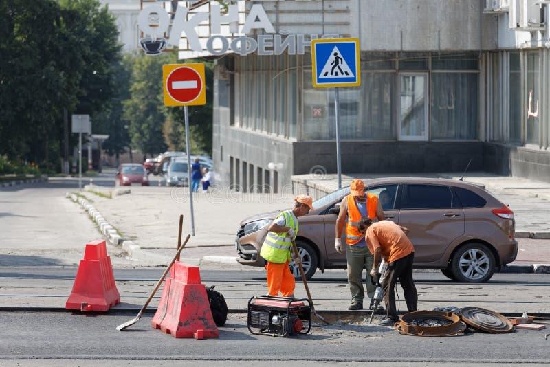 Lavoratori della strada con una pala e un'attrezzatura pneumatica del martello pneumatico che riparano via durante i lavori strad immagine stock libera da diritti