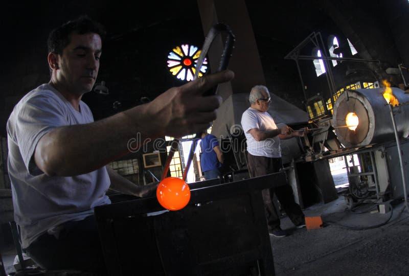 Lavoratori di vetro di blowery all'officina fotografia stock