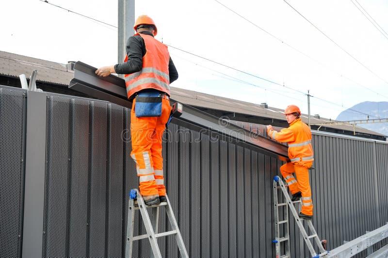 Lavoratori durante l'installazione delle barriere di rumore sulla ferrovia immagini stock