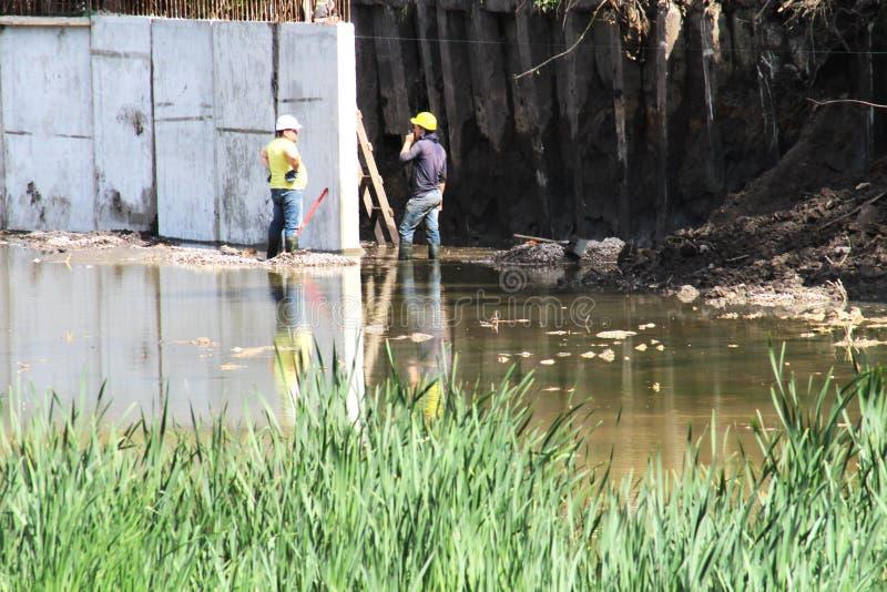 Lavoratori maschii nell'acqua Preparando il sito per lo stagno di contenimento Fondo della foresta del parco immagine stock libera da diritti